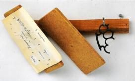 Robert Filiou: 3 fegyver, 1970. Asztaloslécre montírozva, fa, csavarvégű horog, kampósszeg, bokszer, szög, papír, plexi dobozban (45,5 x 45,5 x 13 cm). Németországi magángyűjtemény.