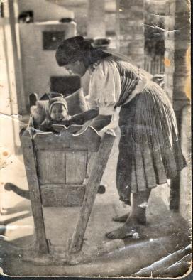 Palóc édesanya ringatja bölcsőben gyermekét